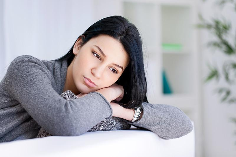 Woman resting head on crossed arms with a concerned look.